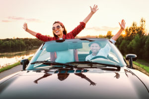 Traveling by car - happy couple in love go by cabriolet car in s