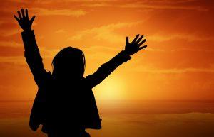 Frau im Sonnenuntergang mit nach oben gestreckten Armen